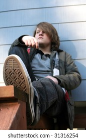 Serious teenage boy sitting on a railing outdoors in winter, from perspective of subject's feet.  Foot is main focus with shallow depth of field.