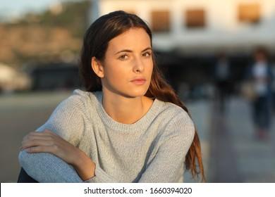 Adolescente seria mirando a una cámara desafiante al atardecer sentada en un pueblo