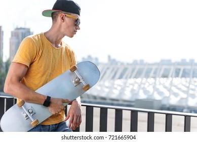 Serious teenager keeping skate in hands