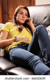 Serious teenager laying on a sofa and talking on phone