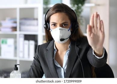 Una mujer con un telemarketer serio, haciendo gestos, deja de evitar el covid-19 con una máscara mirando la cámara sentada en la oficina