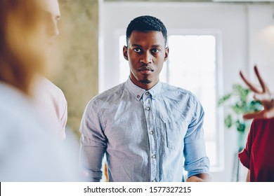 Serious tense African American man in classical shirt angrily looking at speaker on meeting with colleagues in light spacious room