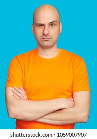 Serious thoughtful bald man wears bright orange shirt, raised eyebrow. Pensive guy isolated on blue background