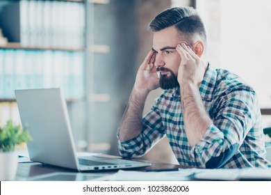 Serious, thoughtful, bearded guy sitting at desk in workplace in front of laptop, touching temples with fingers looking at screen of computer, new ideas, start up, crisis