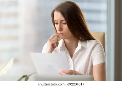 Serious thoughtful businesswoman analyzing important document, focused analyst scrutinizing report, examining company development, thinking of stats result, reading financial statement, head shot