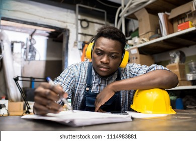 Serious thoughtful handsome young African-American construction engineer in soundproof headphone sitting at table and making notes in diary while planning work in dark room