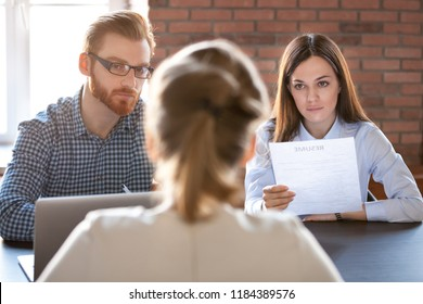 Serious thoughtful hr attentively listening to female applicant at job interview, focused recruiters employers looking making decision about hiring seeker thinking about first impression concept