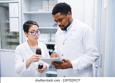 Serious thoughtful multi-ethnic pharmacists in lab coats standing in drugstore and discussing new medications while using tablet to search for information in database