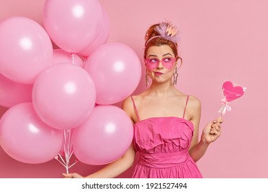 Serious thoughtful redhead woma purses lips thinks about celebration wears trendy sunglasses and dress holds sweet candy and balloons prepares for graduation party isolated over pink background