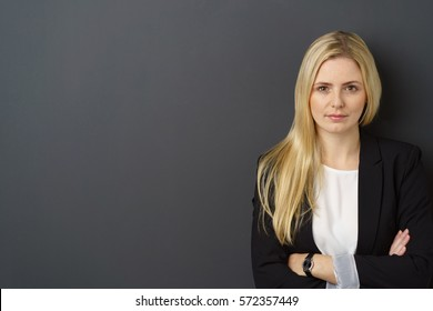Serious thoughtful young businesswoman standing staring at the camera with folded arms over a dark grey background with copy space