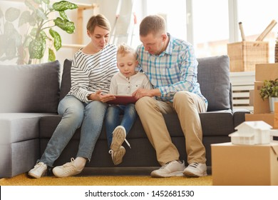 Serious thoughtful young parents sitting around son on sofa and assisting son to do homework online using modern tablet