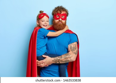 Serious tired dad entertains child on party, pretend being superheroes, have extraordinary power, play together. Little girl in blue t shirt, red cape hugs father has happy look. Family time concept