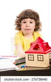 Serious toddler boy sitting at table at kindergarten