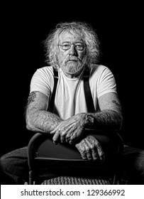 Serious tough old man with wild hair in monochrome isolated on black