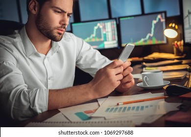 Serious trader using mobile phone app on smartphone for checking stock trading data analysis concept, focused businessman holding cellphone working in office with financial graph on computer monitors