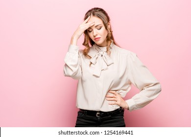 Serious unhappy female has appealing appearance, being sad after quarrel with close person, frowns face in dissatisfaction, isolated over pink studio background. Human negative emotions concept