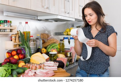 Serious unhappy  woman is standing with check and is sading because of the prices of food at home.