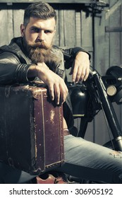 Serious unshaven male biker in leather jacket sitting near motorcycle in garage with big brown old briefcase looking forward on workshop background, vertical picture