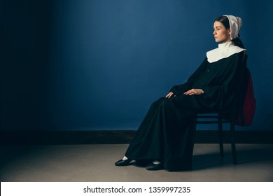 Serious view on sameless day. Medieval young woman as a nun in vintage clothing, white mutch and red bag sitting on the chair on blue background. Waiting for chances. Concept of comparison of eras.