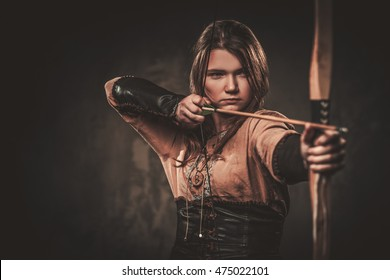 Serious viking with bow and arrow in a traditional warrior clothes, posing on a dark background.
