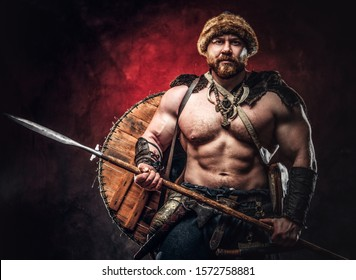 Serious Viking clad in light armor with a shield behind his back holds a spear. Posing on a dark background with red light