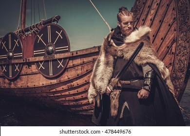 Serious viking warrior with sword standing near Drakkar on the seashore.