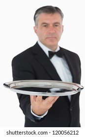 Serious waiter holding silver tray