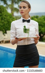 Serious waitress holding drink, waiting for the order