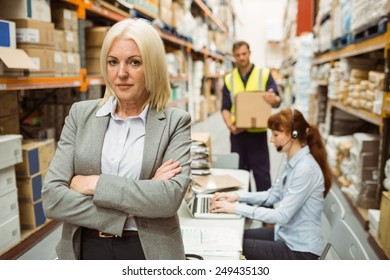 Serious warehouse manager standing arms crossed in a large warehouse