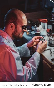 Serious watchmaker  is repairing cutomer's order at his own repairing studio.