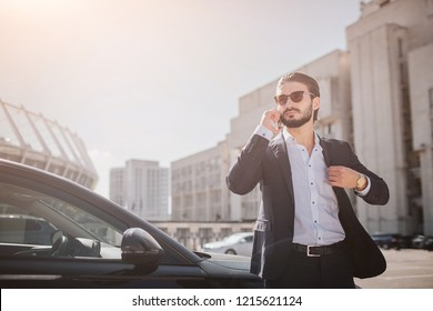 Serious and well-dressed young man stand at car in suite and talks on phone. He holds part of balck jacket. Guy wears sunglasses. It is beautiful and sunny outside.