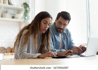 Serious wife and husband planning budget, checking finances, focused young woman using calculator, counting bills or taxes, man using laptop, online banking services, sitting at table in kitchen