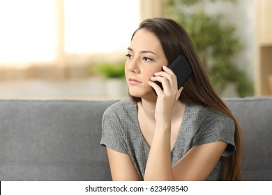 Serious woman attending a phone call sitting on a sofa in the living room at home