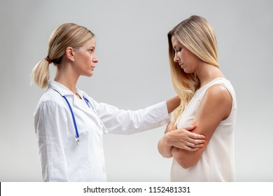 Serious woman doctor showing empathy for a young female patient reaching out a comforting hand to her shoulder in a close up side view