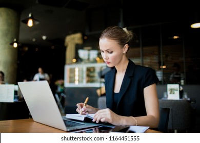 Serious woman economist writing notary in notepad during work on laptop computer while sitting in restaurant during work break. Female employee writing a monthly report in notebook from net-book