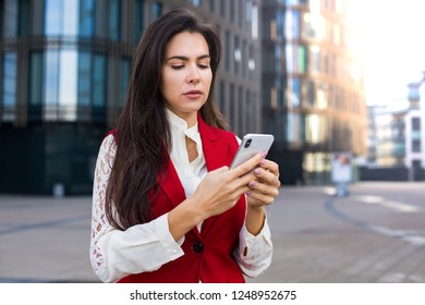 Serious woman employer online chatting on mobile phone while standing against office building with copy space for promotional content. Female CEO using messenger on cell telephone during work break