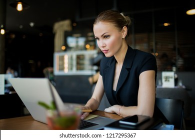 Serious woman financier reading information on stock exchange via modern laptop computer while sitting in restaurant during work break in enterprise. Female jurist having video conference via netbook