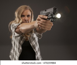 Serious woman with a flashlight and a pistol.