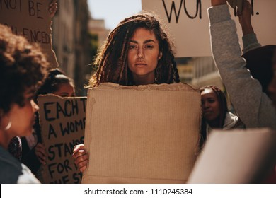Serious woman holding a blank placard during a protest outdoors. Group of female demonstrators on road with banners.