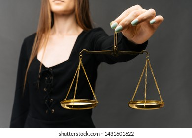 Serious woman holding the justice scale on dark background - image