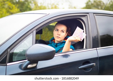 Serious woman holding out drives a car, license and documents, driving her car. Traffic violation concept, stop, document check