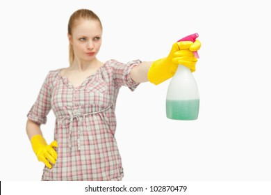 Serious woman holding a spray bottle while looking away against white background