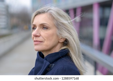 Serious woman looking intently to the side with a thoughtful expression as she stands outdoors in town on a walkway