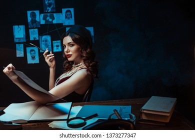 Serious woman with mouthpiece holding dossier and looking at camera in dark office