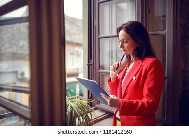Serious woman  occupied with job working near window