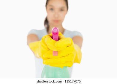 Serious woman pointing a spray bottle at the camera on a white background