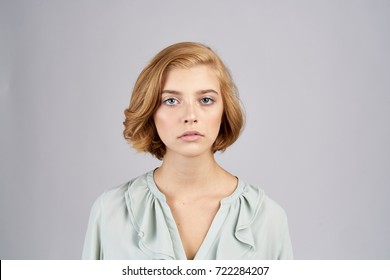 serious woman with short hair looks at the camera on a gray background portrait, beauty, fashion