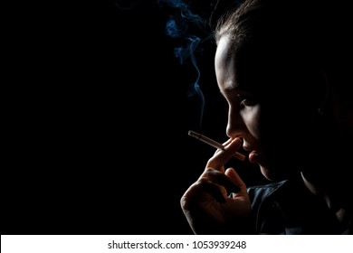 serious woman smoking cigarette on black background, profile view
