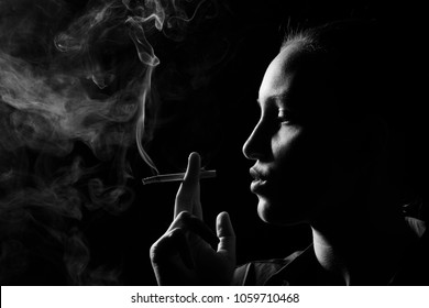serious woman smoking cigarette on black background, profile view, monochrome