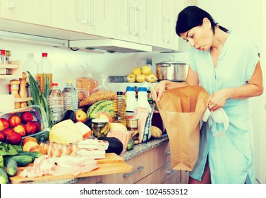 Serious woman is standing with empty bag and is sading because forgot to buy ingridient for recipe at home.